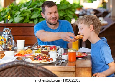 happy family of two, father and son, enjoying delicious breakfast together during vacation or at home