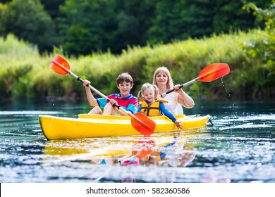 Happy family with two kids enjoying kayak ride on beautiful river. Mother with little girl and teenager boy kayaking on hot summer day. Water sport fun. Canoe and boat for children