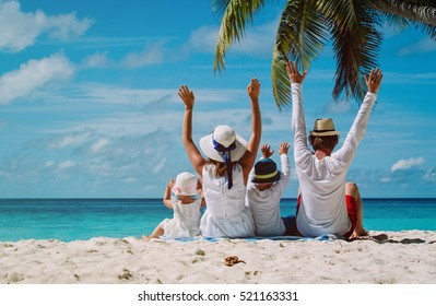 happy family with two kids hands up on the beach - Shutterstock ID 521163331
