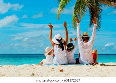 happy family with two kids hands up on beach