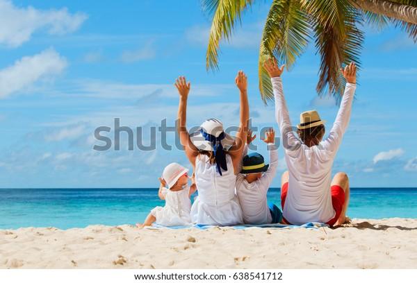 2人の子どもがビーチに手を置いた幸せな家族
