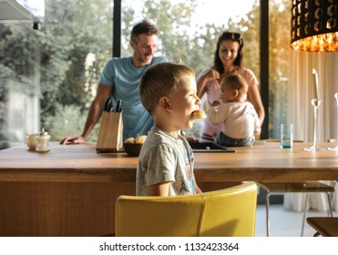 Happy family with two kids having fun in the kitchen.