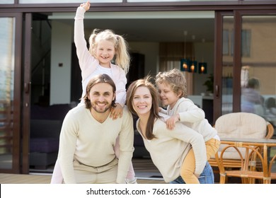 Happy family with two kids having fun together on terrace of modern own new house, smiling parents with little children spending leisure time outside beautiful home looking at camera, mortgage loan