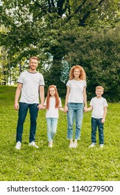 happy family with two kids holding hands and smiling at camera in park