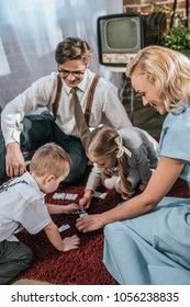 happy family with two kids playing dominoes together at home, 1950s style
