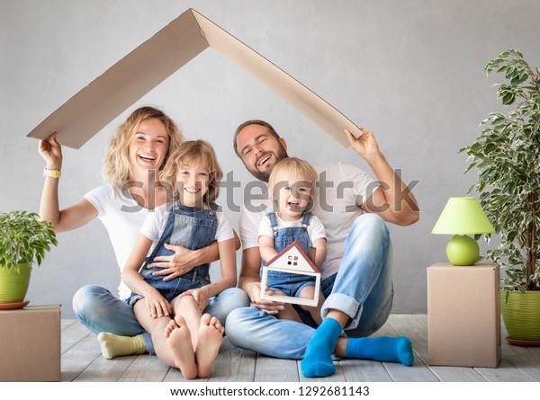 Fröhliche Familie mit zwei Kindern, die in ein neues Zuhause spielen. Vater, Mutter und Kinder, die zusammen Spaß haben. Moving House Day und Immobilienkonzept