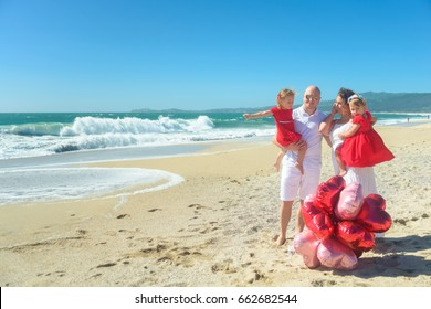 Happy family with two kids posing on the beach