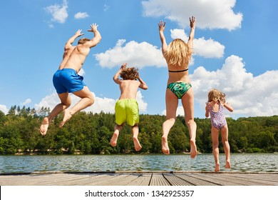 Happy family with two kids in summer on vacation jumps in a lake