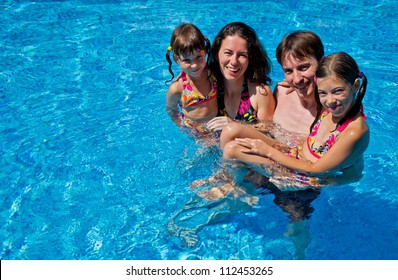 Happy family with  two kids in swimming pool. Smiling parents and children on summer vacation swim and having fun. Family sport, active healthy holiday