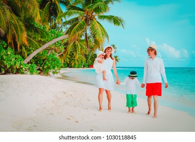happy family with two kids walking on beach