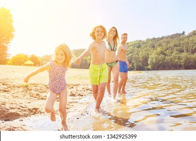 Happy family with two kids while bathing at the lake in summer