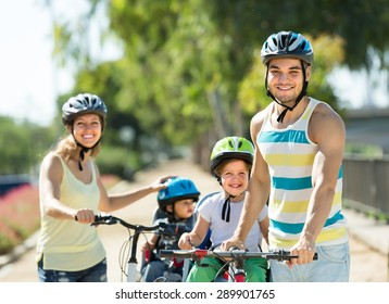 Happy family with two little daughters traveling by bicycles. Focus on man