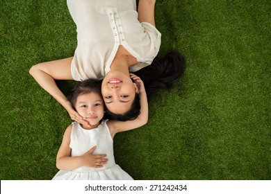 Happy family of two lying on the grass, view from above