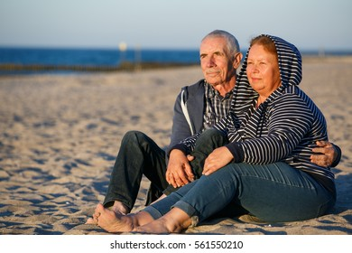 Happy family of two mature people hugging outdoors. Senior smiling  couple sitting barefoot on sand on beach near sea at sunset.