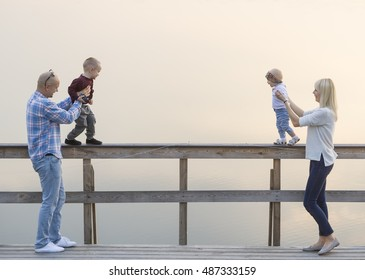 A happy family of two parents and two children, one boys, one baby girl, have a good time on the river jetty. Fog.