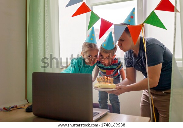 Happy family with two sibling celebrating birthday via internet in quarantine time, self-isolation and family values, online birthday party, selective focus on cake