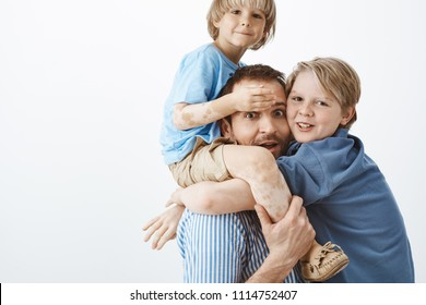 Happy family of two sons and father gazing and smiling at camera. Dad holding cute kid with vitiligo on shoulders while older brother hanging on chest, having fun and share positive emotions