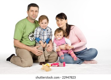 Happy family with two young children sat on floor, white studio background.