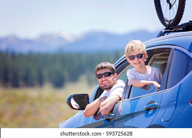 happy family of two, young father and his son, looking out of the car enjoying road trip and active vacation together