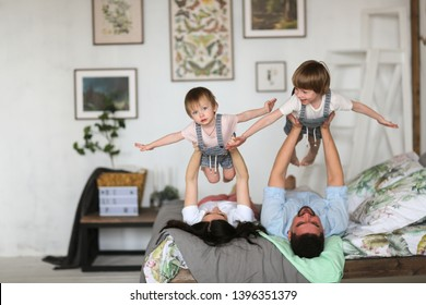 Happy family with two young sons on the bed in the bedroom, Mom and Dad hold the children in their arms in the air, throw them into the air, bright home interior