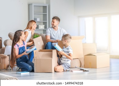 Happy family unpacking belongings in their new house