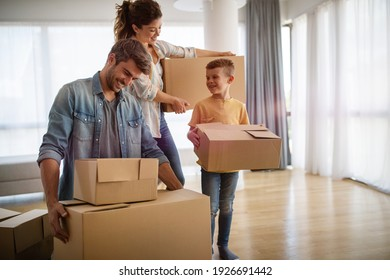Happy family unpacking boxes in new home on road day