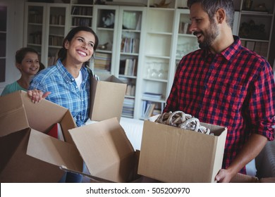 Happy family unpacking cartons in their new house