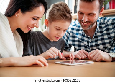 Happy family using digital tablet together at home