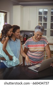 Happy family using laptop in kitchen at home