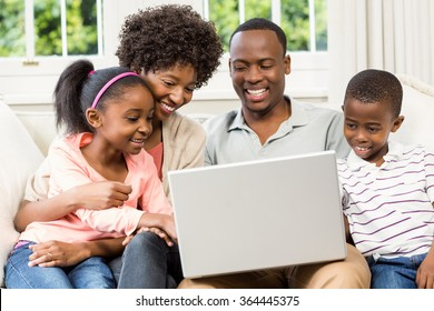 Happy family using laptop on the sofa