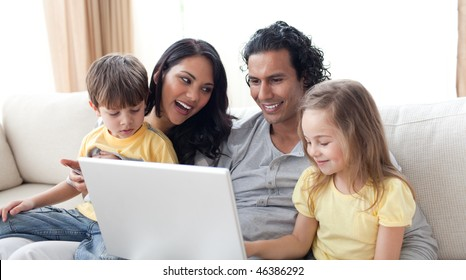 Happy family using laptop on sofa in the living room