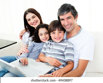Happy family using a laptop sitting on sofa at home