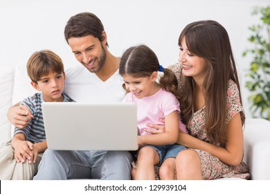 Happy family using laptop together on the couch