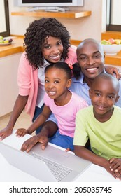 Happy family using the laptop together at home in the kitchen