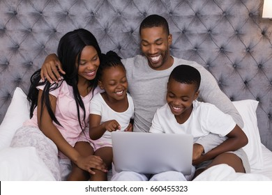 Happy family using laptop together while sitting on bed at home