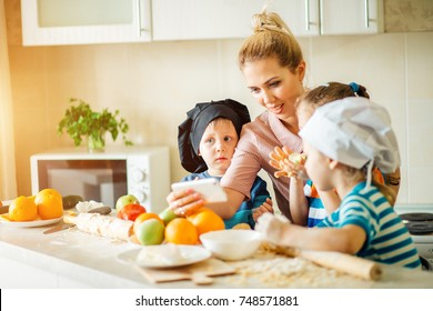 Happy family using mobile phone to find a recipe for cooking while standing at their kitchen