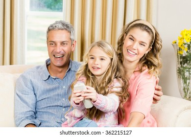 Happy family using remote control at home