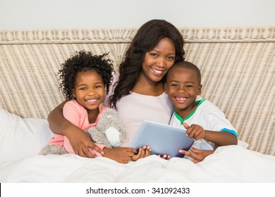 Happy family using tablet in bed at home