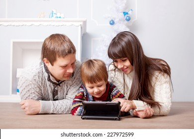 Happy family using the tablet near the fireplace and Christmas tree.