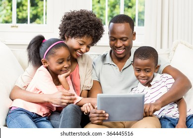 Happy family using tablet on the sofa at home