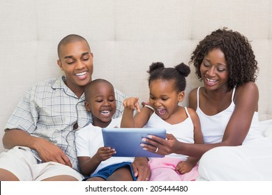 Happy family using tablet together on bed at home in the bedroom