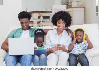 Happy family using technologies on the couch at home in the living room
