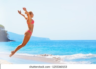 Happy family vacation. Girl in bikini jump high with spreading hand into mid air above water pool and breaking sea surf. Travel adventure lifestyle on summer beach holiday with kids on tropical island