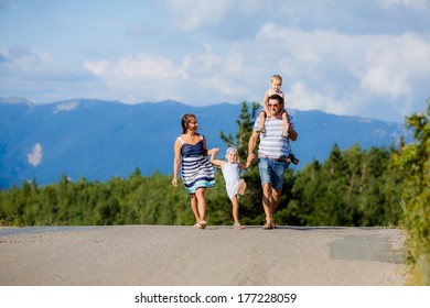 happy family walking along a mountain road