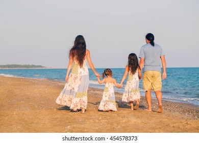 Happy family walking along the sea on the beach. Summer holidays concept.
