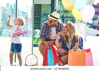 Happy family walking along the shopping mall with shopping bags and balloons.