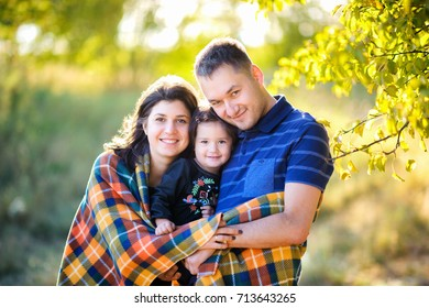 happy family walking in an autumn park at sunset, hiding in a padded hug and smiling