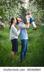 Happy Family Walking In A Blooming Garden.