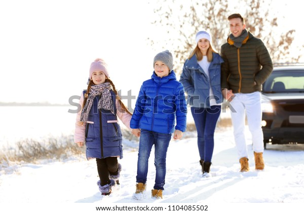 Happy family walking in countryside on winter day