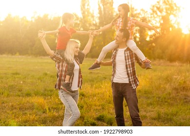 Happy family walking in field and looking at sunset